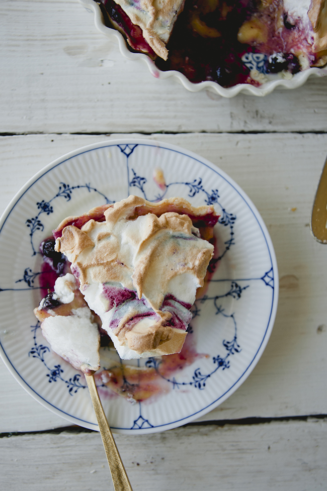 SLICE OF HUCKLEBERRY LEMON MERINGUE PIE SERVED ON BLUE AND WHITE PLATE  // The Kitchy Kitchen
